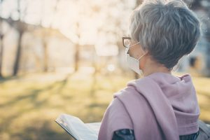 Woman reading Bible with mask on