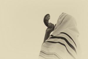 man blowing shofar at end of Yom Kippur